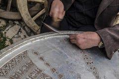 工作在一块铜版的老人 免版税图库摄影