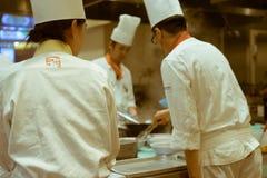 工作在一家日本餐馆,东京,日本的厨房里的厨师 图库摄影
