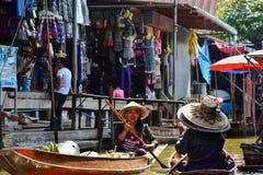 工作在一条小船的泰国妇女在浮动市场附近的曼谷上 免版税库存图片