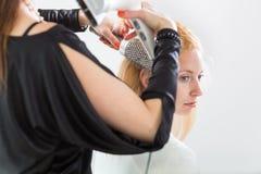 工作在一根少妇的头发的美发师/发型艺术家 图库摄影