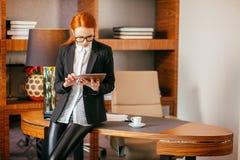 工作在一种数字式片剂的可爱的女实业家在办公室 免版税库存图片