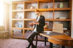 工作在一种数字式片剂的可爱的女实业家在办公室 免版税图库摄影