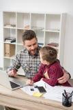 工作在与儿子的桌上的商人自由职业者 免版税库存照片