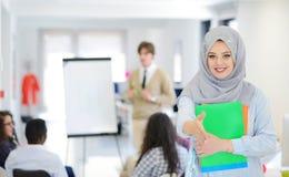 工作在与她的同事的队的阿拉伯女商人在起始的办公室 图库摄影