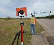 工作在与安全背心和安全帽的领域的测量员 库存图片