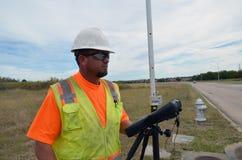 工作在与安全背心和安全帽的领域的测量员 库存照片