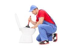 工作在与柱塞的一间洗手间的男性水管工 库存照片