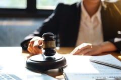 工作在与法官惊堂木的律师事务所的专业女性律师在木桌上 法律的概念 库存图片