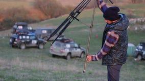 工作在与照相机和三脚架的自然的年轻摄影师 影视素材