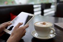 工作在与片剂和一杯咖啡的一个咖啡馆 库存图片