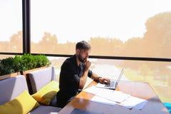 工作在与纸和膝上型计算机的咖啡馆桌上的施工技术员 图库摄影