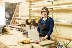 工作在与膝上型计算机的一woodshop的妇女 免版税图库摄影