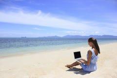工作在与膝上型计算机的海滩的Bussines妇女 免版税图库摄影