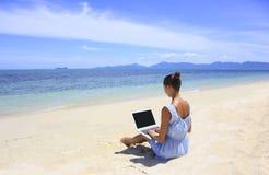 工作在与膝上型计算机的海滩的Bussines妇女 免版税库存照片