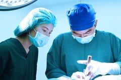 工作在与艺术照明设备和蓝色过滤器的手术室作为的两位兽医医生 库存照片