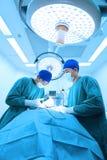 工作在与艺术照明设备和蓝色过滤器的手术室作为的两位兽医医生 免版税库存照片