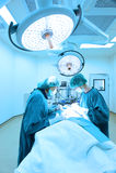 工作在与艺术照明设备和蓝色过滤器的手术室作为的两位兽医医生 免版税库存图片