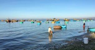 工作在与许多渔船的海滩的人们在藩朗,越南 免版税库存照片