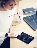 工作在与移动设备的木桌上的年轻美丽的妇女顶视图  女性手感人的数字式片剂 免版税库存照片