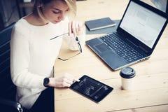 工作在与移动设备的木桌上的年轻美丽的妇女顶视图  女性手感人的数字式片剂 图库摄影
