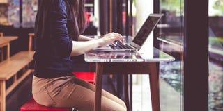 工作在与lapto的一家咖啡店的美丽的年轻亚裔女孩 免版税库存图片