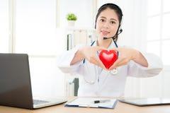 工作在个人办公室的微笑的女性医生 库存图片