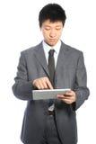工作在个人计算机片剂的新亚洲生意人 库存图片