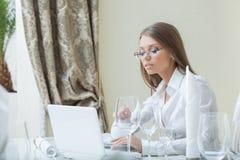 工作在个人计算机的女商人在餐馆 免版税库存照片