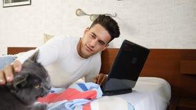 工作在个人计算机的年轻人,宠爱宠物猫 库存照片