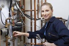工作在中央系统暖气锅炉的女性水管工 库存图片