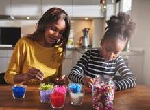 工作在串珠的工艺的孩子和父母 免版税库存照片