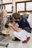 工作在义肢腿零件的技术员 免版税库存照片