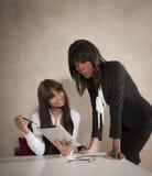 工作在书桌的两位年轻商业主管 免版税库存照片