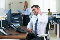 工作在书桌的商人遭受脖子痛 免版税图库摄影