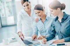 工作在书桌的女商人队 免版税库存照片