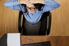 工作在书桌的妇女从上面被射击 免版税库存图片