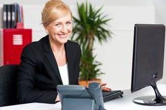 工作在书桌的快乐的年迈的妇女 免版税库存图片