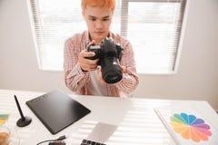 工作在书桌的摄影师在现代办公室 免版税库存图片