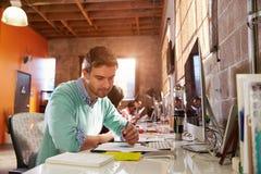 工作在书桌的设计师队在现代办公室 库存照片