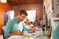 工作在书桌的设计师队在现代办公室 免版税库存照片