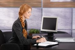 工作在书桌的年轻女实业家 库存照片