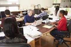 工作在书桌的建筑师队在办公室 免版税库存图片