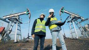 工作在井架,抽油装置附近的工程师 石油生产产业概念 股票视频