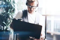 工作在他的举行在手上的数字式片剂的现代办公室的商人 佩带音频耳机的成人银行家和 图库摄影