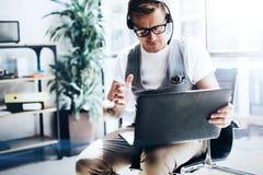工作在他的举行在手上的数字式片剂的现代办公室的商人 佩带音频耳机的英俊的年轻人和 免版税库存照片
