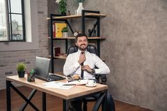 工作在他的书桌的年轻时髦的英俊的商人在固定他领带和微笑的办公室 免版税库存照片