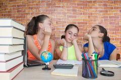 工作在他的家庭作业的三个女孩 免版税图库摄影