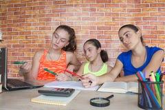 工作在他的家庭作业的三个女孩 库存照片
