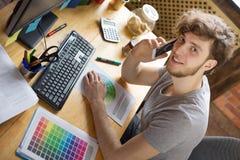 工作在他的工作场所的年轻微笑的人 库存照片
