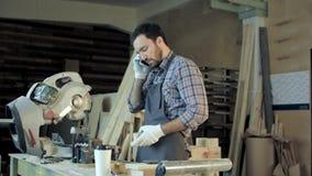 工作在他的工艺的木匠在一个多灰尘的车间和讲电话 免版税库存照片